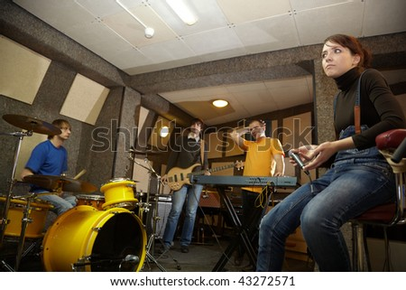 a rock band is working in studio. practice pause - stock photo