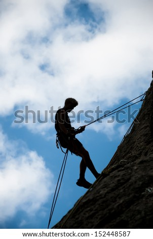 A rock climber ascends to the top - stock photo