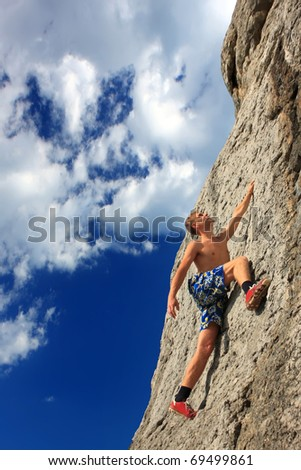 A rock climber on a rock against the blue sky - stock photo