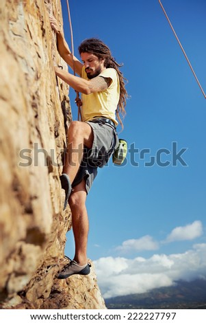A rockclimber finding a foothold on the steep mountain he's climbing - stock photo