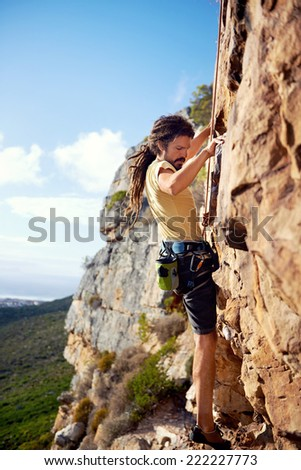 A rockclimbing guy with dreadlocks finding a foothold on a steep mountain - stock photo