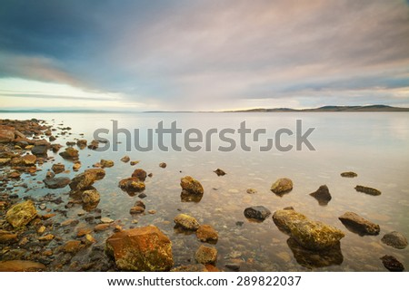 A rocky coastline disappears into the calm clear water. - stock photo