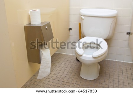 A roll of toilet paper next to a toilet in a bathroom - stock photo