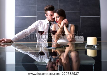 A romantic couple with a glass of wine in the dining room.  - stock photo