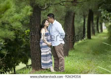 A romantic husband kissing his pregnant wife under pine tree - stock photo