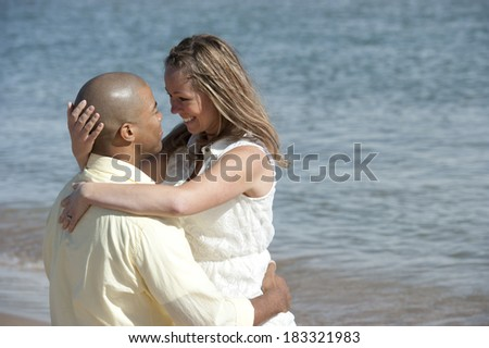 A romantic interracial couple sitting at the beach on a sunny day. - stock photo
