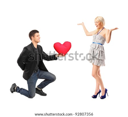 A romantic man on his knees holding a red heart shaped pillow and an excited blond woman isolated on white background - stock photo