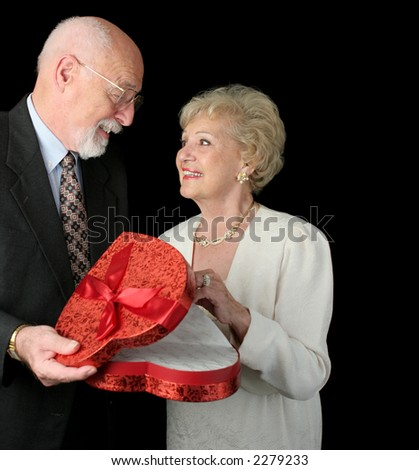 A romantic senior couple on Valentines Day.  Black background. - stock photo