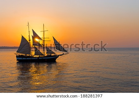 A romantic sunset with a sailing ship seen at the greek islands - stock photo
