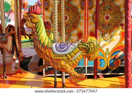 A Rooster Chicken Seat on a Fun Fair Carousel Ride. - stock photo