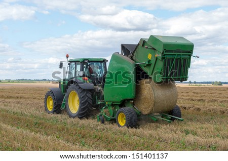 A round baler discharges a fresh wheat bale during harvesting. - stock photo