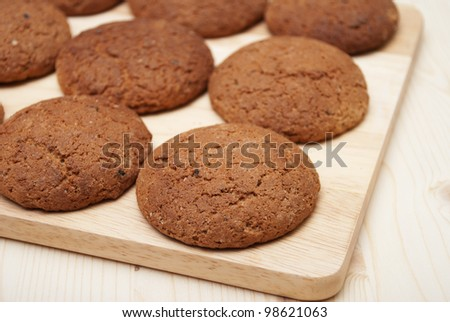 A round oatmeal cookie is in rows on wooden board - stock photo