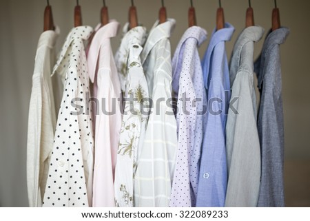 A row of assorted business shirts for women on hangers in a closet. - stock photo