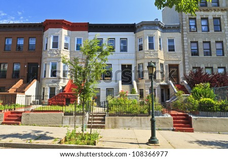 A row of attached apartment buildings on Eastern Parkway in the Crown Heights neighborhood of Brooklyn, NY - stock photo
