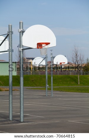A row of basketball hoops on a blacktop - stock photo