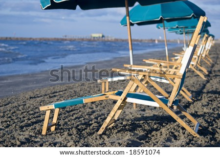 A row of beach chairs lined up on a beach. - stock photo
