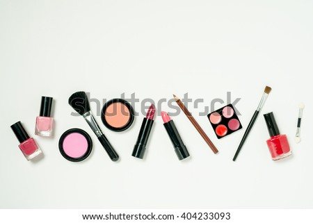 A row of beauty cometics that includes nail lacquer, lipstick, lip color, cheek blush, and brushes. - stock photo