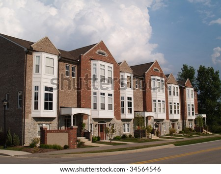 A row of brick condos or townhouses with bay windows beside a street. - stock photo