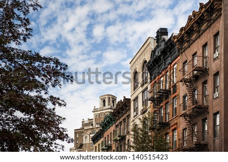a row of brownstone buildings in a large city - stock photo