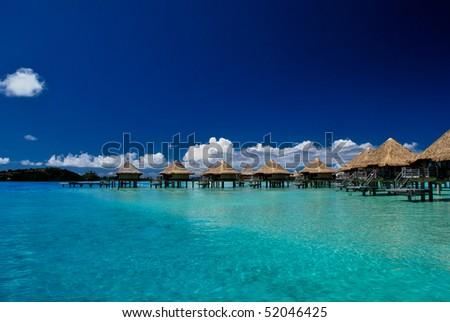 A row of bungalows on a blue lagoon in Bora Bora - stock photo