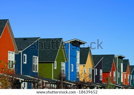 A row of colorful new houses against a blue sky - stock photo