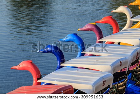 A row of colorful pedal boats. - stock photo