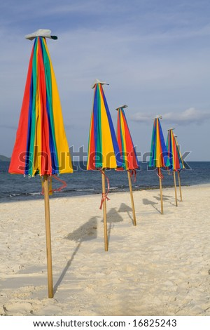 A row of colorful umbrellas on the beach - stock photo
