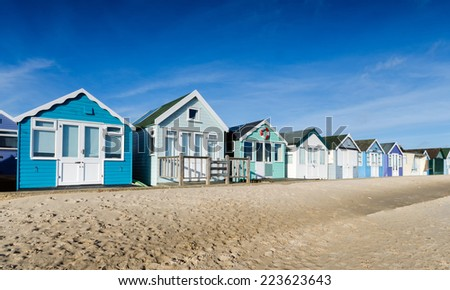 A row of colourful beach huts on a sandy beach - stock photo