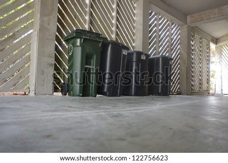 A row of dark green trash bins in the garage of a stilted beach. - stock photo