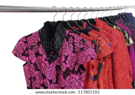 A row of evening gown clothes hanging on hangers - stock photo