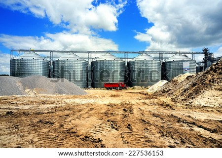 A row of granaries against the blue sky. Silos for wheat storage and drying. A red lorry in front of the granaries.  - stock photo