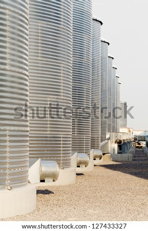 A row of granaries for storing wheat and other cereal grains. The ventilation systems are highly visible. - stock photo