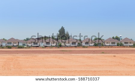A row of new houses in construction site. - stock photo