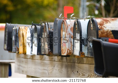 A row of old rusty mailboxes - stock photo