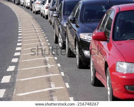 A row of parked cars curving around bend in road - stock photo