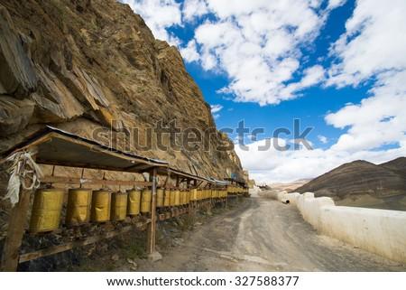 A row of prayer wheels on the way to Shegar Dzong (Chode Monastery) in Tingri, Tibet - stock photo
