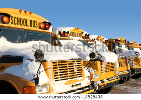 A row of school buses covered in snow. - stock photo