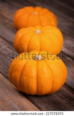A row of three miniature pumpkins on an old wood background. Intentional shallow depth of field. - stock photo
