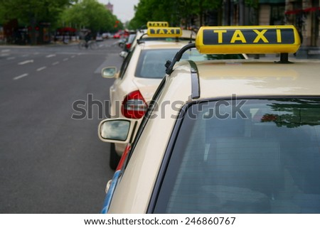 A row of three taxis waiting in line for customers on Berlin's Unter den Linden, TAXI sign big in right area of the frame, on a grey day - stock photo