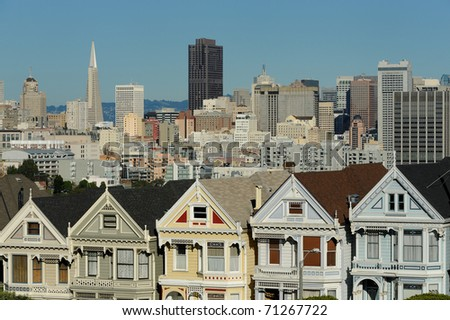 """A row of Victorian houses, known as the """"Painted Ladies"""" with downtown in the background as viewed from Alamo Square in San Francisco, California - stock photo"""