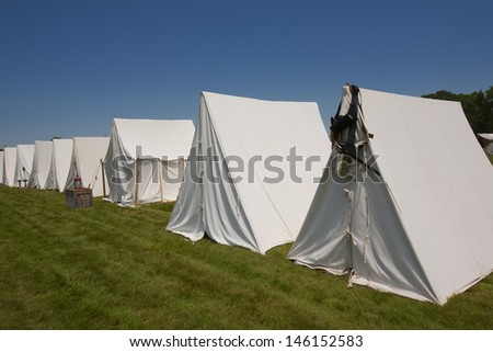 A row of white canvas tents used for the War of 1812 and Revolutionary War Reenactments. - stock photo