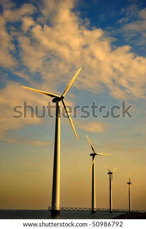 A row of wind turbines in the sea at sunset - stock photo