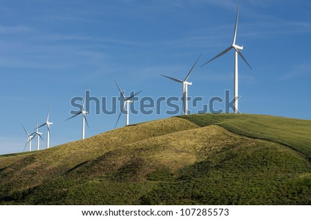 A row of wind turbines on a sunny hill - stock photo