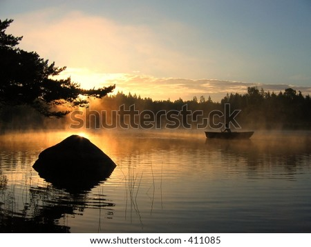 A rowing boat in the morning mist with the sun rising above the trees. - stock photo