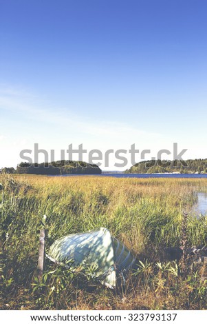 A rowing boat on the beach by the lake in the autumn. The focus point is on the boat in the front part. Image also has a vintage effect applied. - stock photo