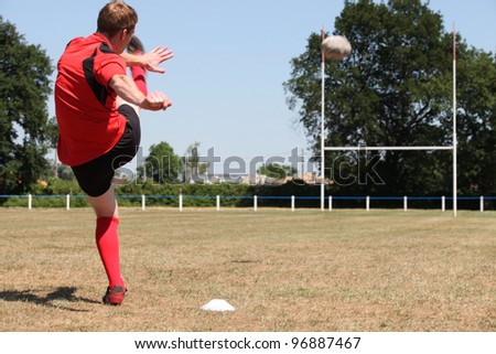 A rugby player kicking a ball - stock photo
