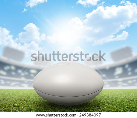 A rugby stadium with a generic white rugby ball on a marked green grass pitch in the daytime under a blue sky - stock photo