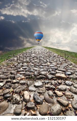 A rugged cobblestone trail up a hill to a hot air balloon takeoff platform.  - stock photo