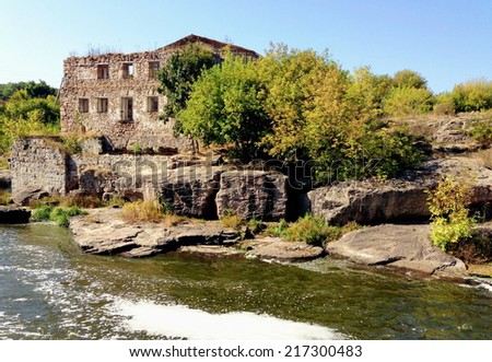A ruined building in the forrest on a mountain river - stock photo