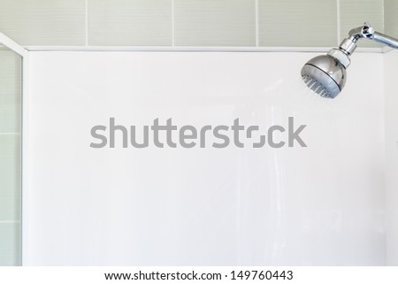 A running shower with a blank white walls and green tiles. Plenty of space for your own message - stock photo